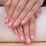 Beauty treatment photo of nice manicured woman fingernails. Very nice pink French manicure with silver detail.